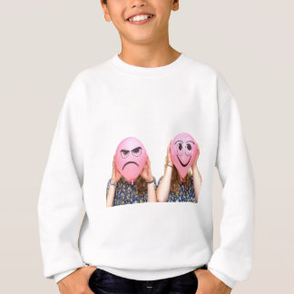 Two girls holding pink balloons with expressions sweatshirt