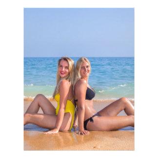 Two girls sit on beach near blue sea.JPG Letterhead
