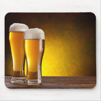Two glasses of beers on a wooden table mouse pad