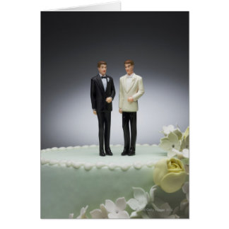 Two groom figurines on top of wedding cake card