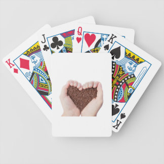 Two hands holding chocolate sprinkles poker deck
