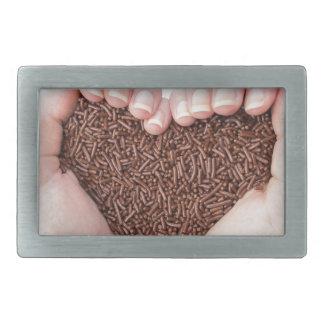 Two hands holding chocolate sprinkles rectangular belt buckles
