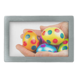 Two hands holding  painted easter eggs on white belt buckles