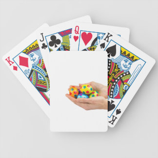 Two hands holding  painted easter eggs on white bicycle playing cards