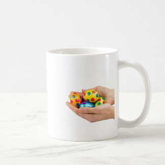 Two hands holding  painted easter eggs on white coffee mug