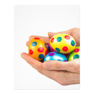Two hands holding  painted easter eggs on white letterhead
