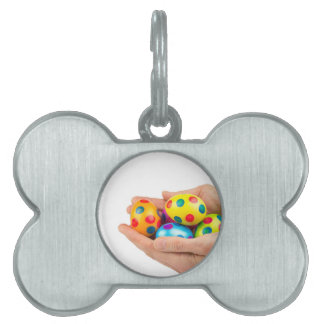 Two hands holding  painted easter eggs on white pet tags