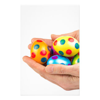 Two hands holding  painted easter eggs on white stationery