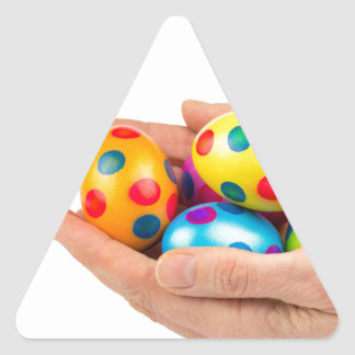 Two hands holding  painted easter eggs on white triangle sticker