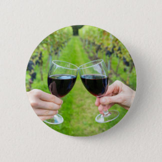 Two hands toasting with wine glasses in vineyard 2 inch round button