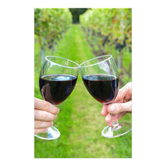 Two hands toasting with wine glasses in vineyard stationery design