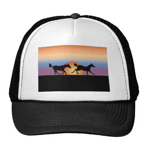 Two horses running against a sunrise hats