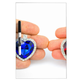 Two jewelry hearts on hand of man and woman dry erase board