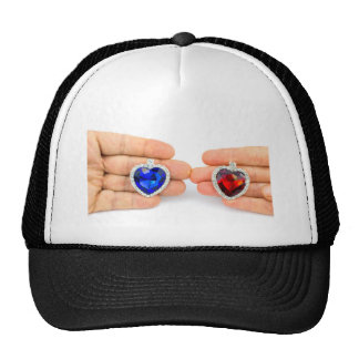 Two jewelry hearts on hand of man and woman trucker hat