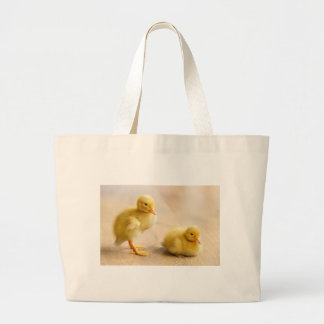 Two newborn yellow ducklings on wooden floor large tote bag