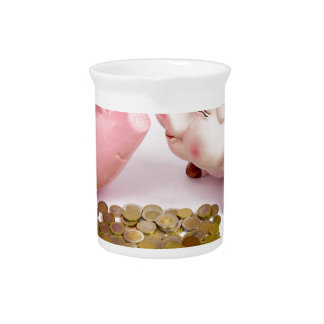 Two piggy banks with euro coins on white beverage pitchers