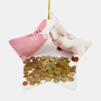 Two piggy banks with euro coins on white ceramic ornament