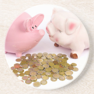 Two piggy banks with euro coins on white coaster