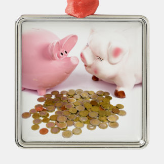 Two piggy banks with euro coins on white metal ornament