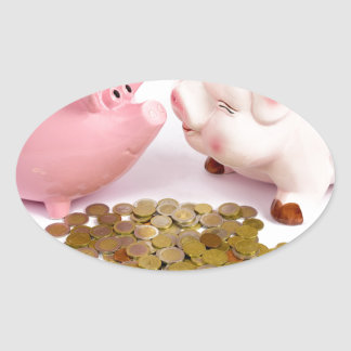 Two piggy banks with euro coins on white oval sticker