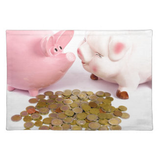 Two piggy banks with euro coins on white placemat
