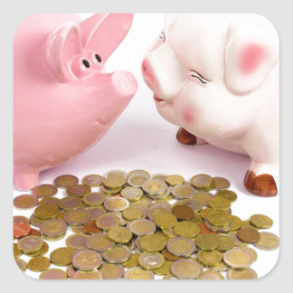 Two piggy banks with euro coins on white square sticker