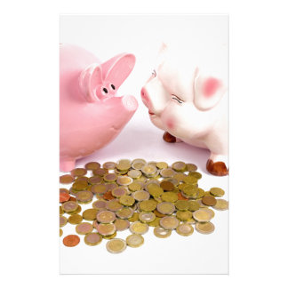 Two piggy banks with euro coins on white stationery
