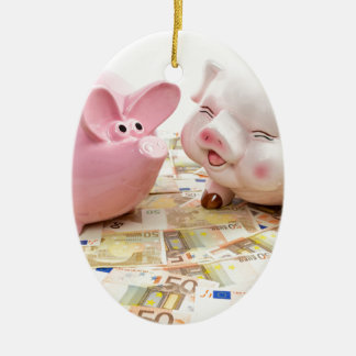 Two pink piggy banks on spread euro notes ceramic oval ornament