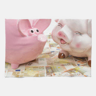Two pink piggy banks on spread euro notes kitchen towels
