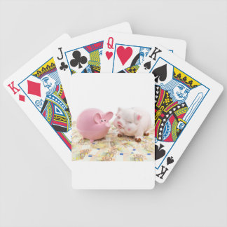 Two pink piggy banks on spread euro notes poker deck