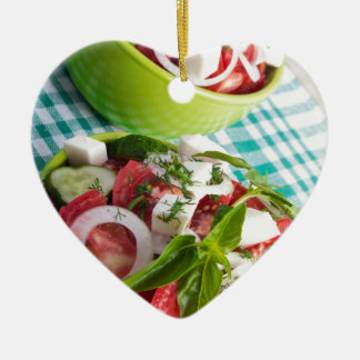 Two portions of useful vegetarian meal closeup ceramic heart ornament