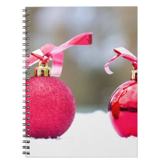 Two red christmas balls outside in snow notebook