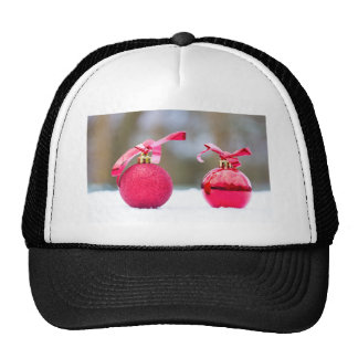 Two red christmas balls outside in snow trucker hat