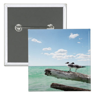 Two seagulls sitting on a dead tree sticking out 2 inch square button
