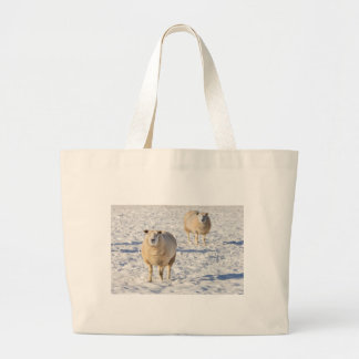 Two sheep standing in snow during winter large tote bag