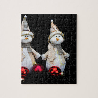Two snowmen figurines with red baubles on black jigsaw puzzle