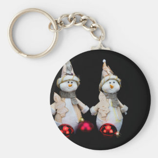 Two snowmen figurines with red baubles on black keychain