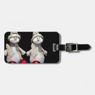Two snowmen figurines with red baubles on black luggage tag