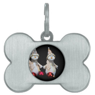 Two snowmen figurines with red baubles on black pet name tag