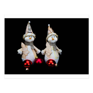 Two snowmen figurines with red baubles on black postcard