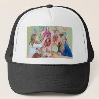 Two students learning model human body in biology. trucker hat