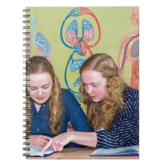 Two students learning with books in biology lesson