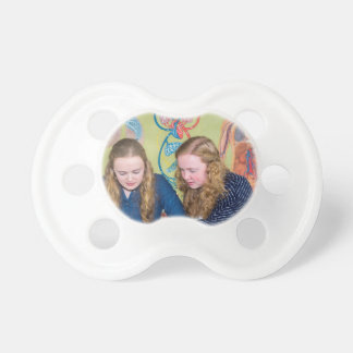 Two students learning with books in biology lesson baby pacifiers
