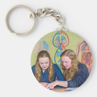Two students learning with books in biology lesson basic round button keychain