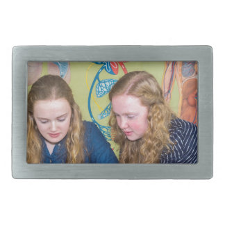 Two students learning with books in biology lesson belt buckle