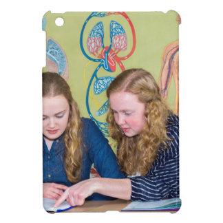 Two students learning with books in biology lesson iPad mini cases