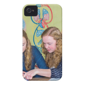 Two students learning with books in biology lesson iPhone 4 covers