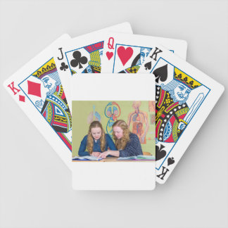 Two students learning with books in biology lesson poker deck
