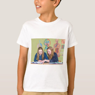 Two students learning with books in biology lesson T-Shirt