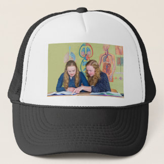 Two students learning with books in biology lesson trucker hat